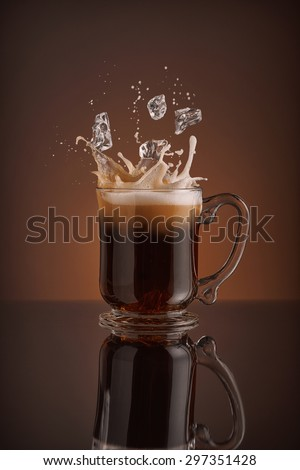 Splash of  ice coffee drink on a brown background. Refreshing Iced cappuccino liquid drink pouring into a mug, cup with ice cubes. Cold beverage wave. Close-up design liquor milk, coffee and ice.