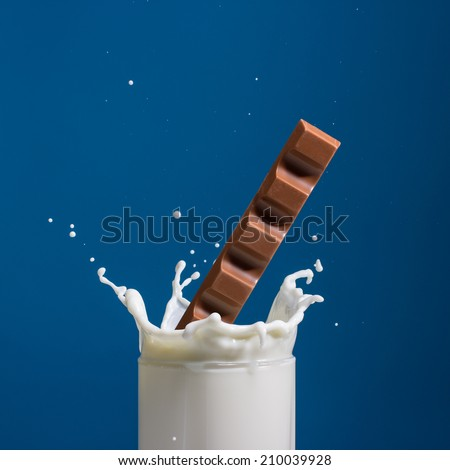 Splash of milk, caused by falling into a chocolate . Isolated on a blue background. - stock photo