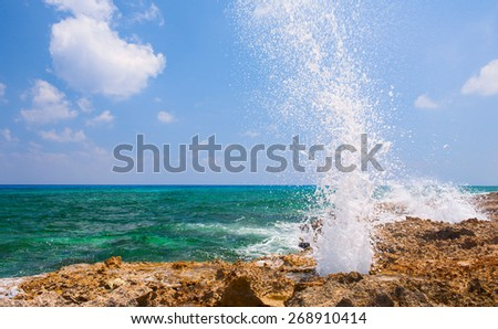 Splash of ocean wave on the rocky beach. Cozumel, Mexico. - stock photo