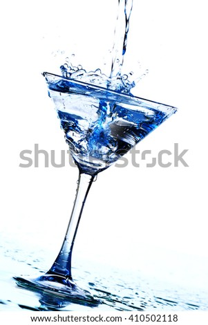 Splash of pouring cocktail into martini glass - stock photo