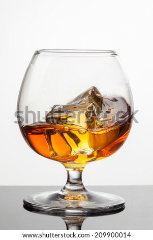 Splash of whiskey with ice in glass isolated on white background. Raw image, no postproduction - stock photo