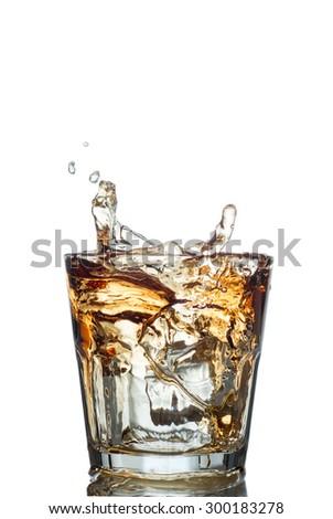 splash of whiskey with ice osolated on white. - stock photo