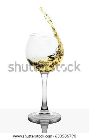 Splash of white wine in the cup filling on a white background