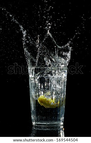 Splash water like vodka in the glass on dark background - stock photo