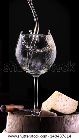 Splash white wine  against a black background on barrel with cheese, cork and corkscrew - stock photo