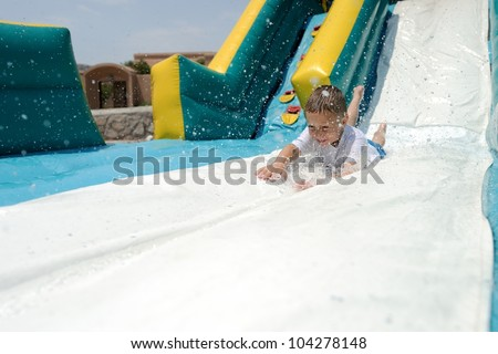 Splashdown! Young boy sliding down an inflatable water slide feet first while splashing water.
