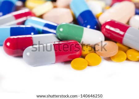 Splashed capsules on white background