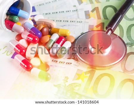 Splashed one hundred euro bills and pills - stock photo