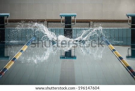 Splashes after swimmers jump in a swimming pool  - stock photo