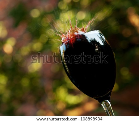 splashes of red wine in the glass - stock photo