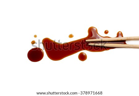 splashes of soy sauce and chopsticks isolated on white. wooden chopsticks dipped in soy sauce spilled. splashes and drops of isolated on white background. flat lay, top view - stock photo