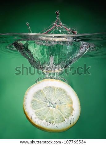 splashing lemon into fresh water - stock photo