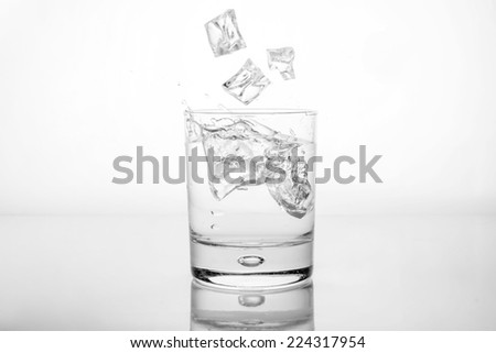Splashing of water with ice in glass - stock photo
