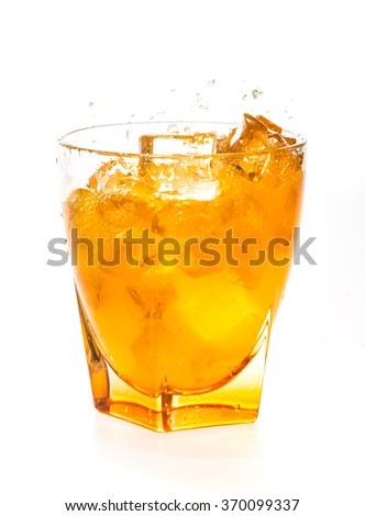 splashing orange juice in glass over white background
