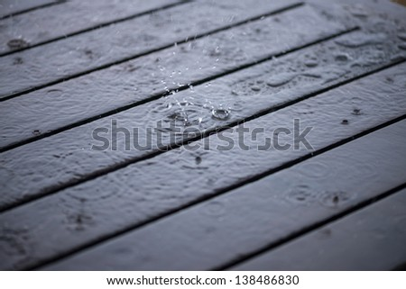 Splashing rain water droplets on wet wooden deck background - stock photo