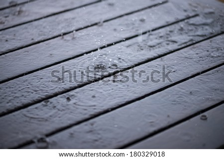 Splashing rain water droplets on wooden deck close up  - stock photo