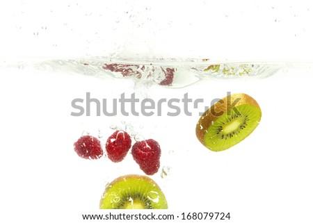 Splashing raspberries and kiwis - stock photo