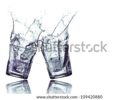 Splashing water from two glasses isolated in white - stock photo