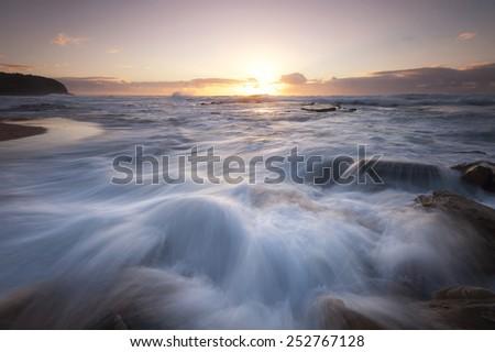 splashing wave during sunrise - stock photo