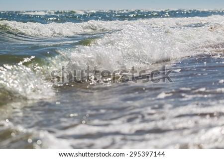 Splashing waves on sea shore. Photo of sea photographed on shallow depth of field - stock photo