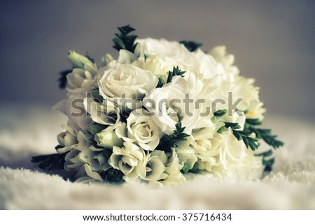 Splendid graceful bridal floral decor bunch of champagne tulips and white roses flowers with green leaves for wedding ceremony anniversary day on light background closeup indoor, horizontal picture - stock photo