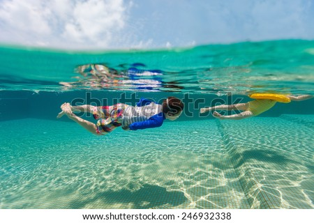 Split above and underwater photo of adorable kids having fun swimming at pool on summer vacation - stock photo