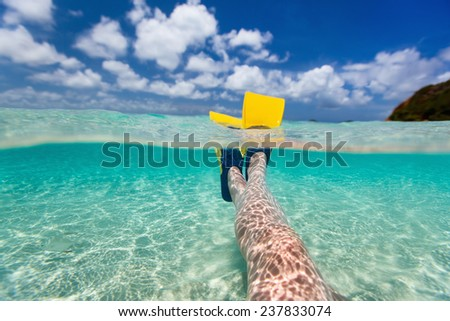 Split above and underwater photo of woman legs with fins at shallow water on tropical beach - stock photo