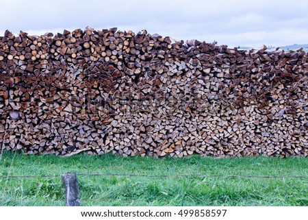 Split firewood neatly stacked high as sustainable renewable heating energy resource supplied by forestry industry