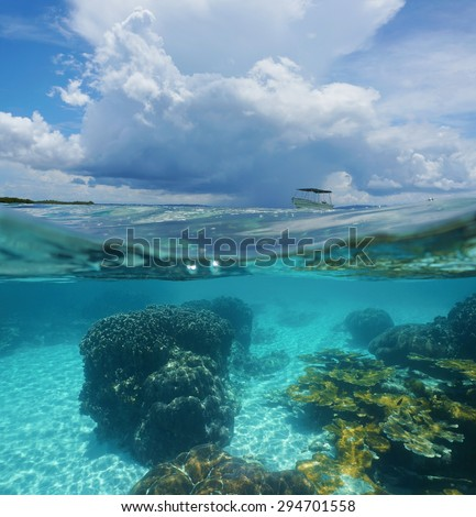 Split image with corals underwater and threatening cloud with a boat above waterline, Caribbean sea, Panama - stock photo