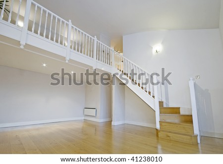 split level living room with wooden stair case - stock photo