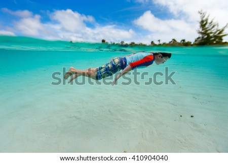 Split of above and underwater photo of cute little boy swimming in ocean - stock photo