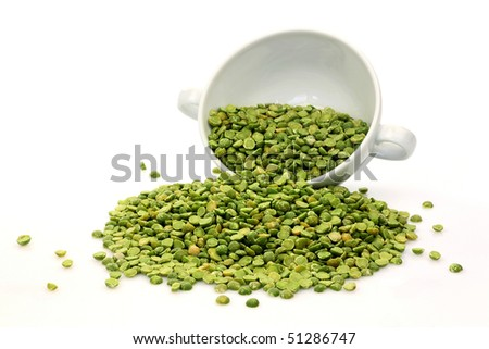 split peas coming out of a white bowl on a white background - stock photo