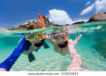 Split photo of mother and son family snorkeling in turquoise ocean water at tropical island - stock photo