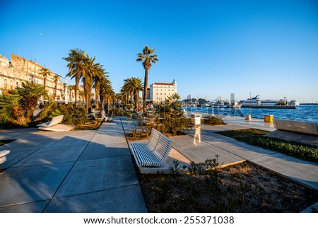 Split's promenade with benches, palms and sea in the evening in Croatia