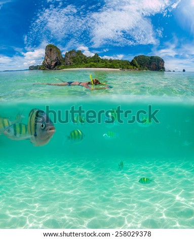 Split shot half above and underwater of a woman snorkeling in Thailand - stock photo