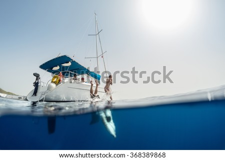 Split shot of the couple jumping into the clear sea from the sail boat - stock photo
