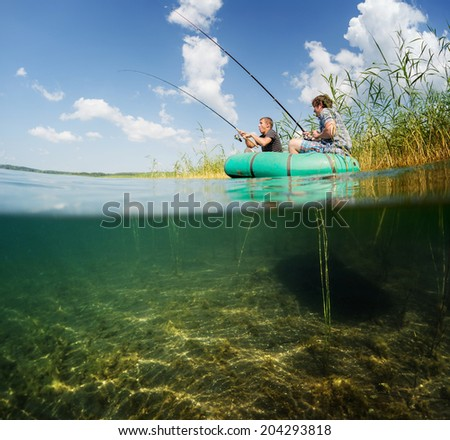 Split shot of two fishermen in the boat in reed's thicket and underwater view of the bottom - stock photo
