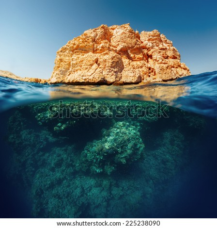 Split shot with coral reef underwater and rocky land of the Ras Muhammad National Park, Red Sea, Egypt - stock photo