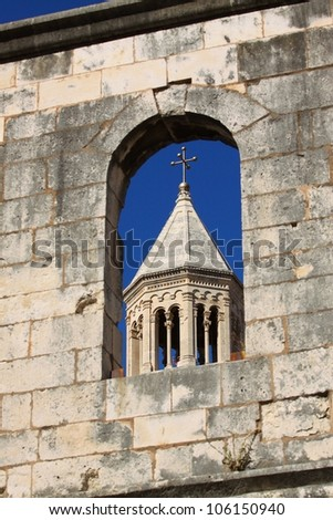 Split stone walls with window and cathedral tower view - stock photo