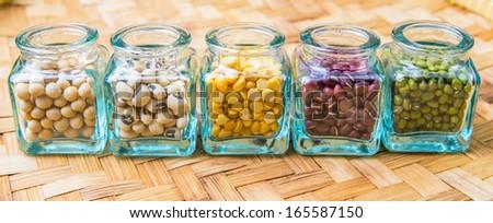 Split toor dal, black eyed peas, soya bean, mung bean, azuki bean in a small  bottles. - stock photo