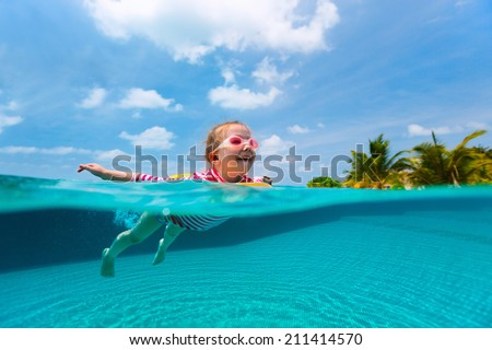 Split underwater photo of adorable little girl with yellow inflatable ring swimming in a pool on summer vacation - stock photo