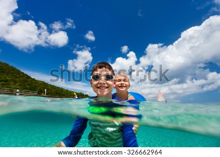 Split underwater photo of kids adorable little girl and cute boy splashing in a tropical ocean water during summer vacation - stock photo