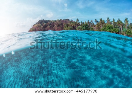 Split underwater shoot of a sandy sea bottom and green tropical island with cloudy sky above sea surface - stock photo