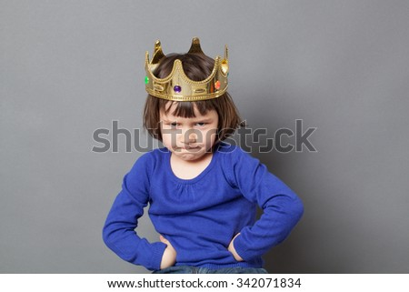 spoilt kid concept - adorable preschool child with golden crown on head putting hands on hips for confident mollycoddled little king or queen metaphor,studio shot - stock photo