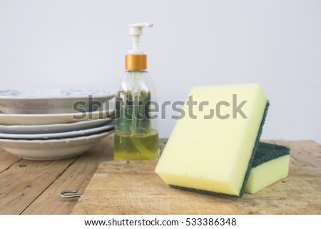 Sponge and dishwashing liquid on wood table