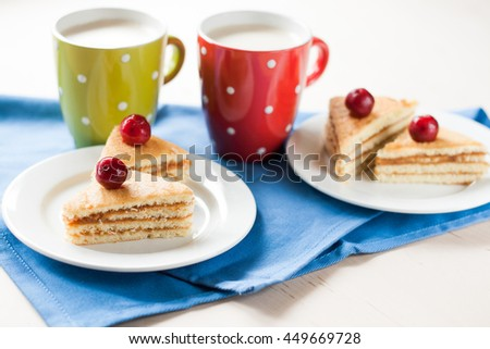 Sponge cake with cherries on a plate and cup of coffee - stock photo