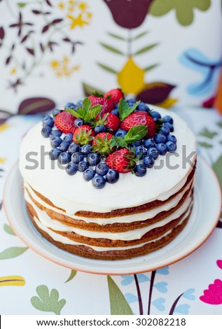 Sponge naked carrot cake with buttercream and mascarpone frosting and fruits decor - stock photo