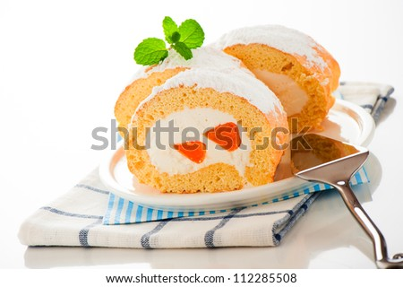 Sponge roll cake with orange cream and fresh mandarin. Fresh Mint and icing sugar as decoration on the top. - stock photo
