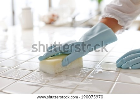 Sponge With Soap Suds Wiping The Top Of Tiles Stock Photo