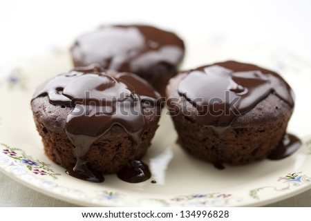 spongecake or muffin with chocolate sauce and crystallised flowers - stock photo